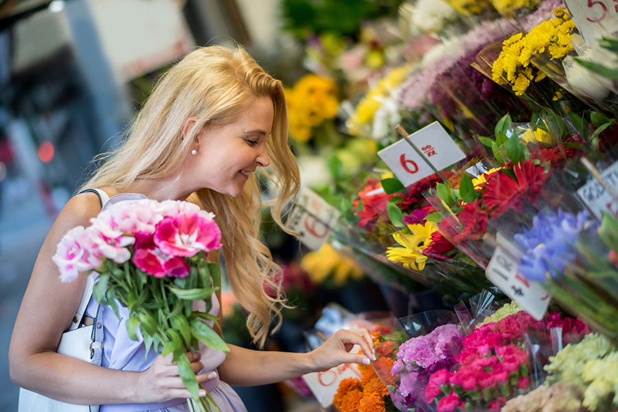 Women is buying flowers at flower shop